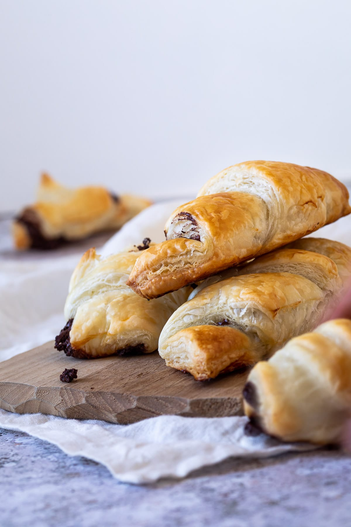 Flaky chocolate croissants on a wooden board with a croissant blurred in the backgroound