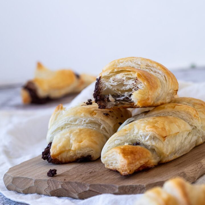 In focus a half chocolate croissants with flaky layers .