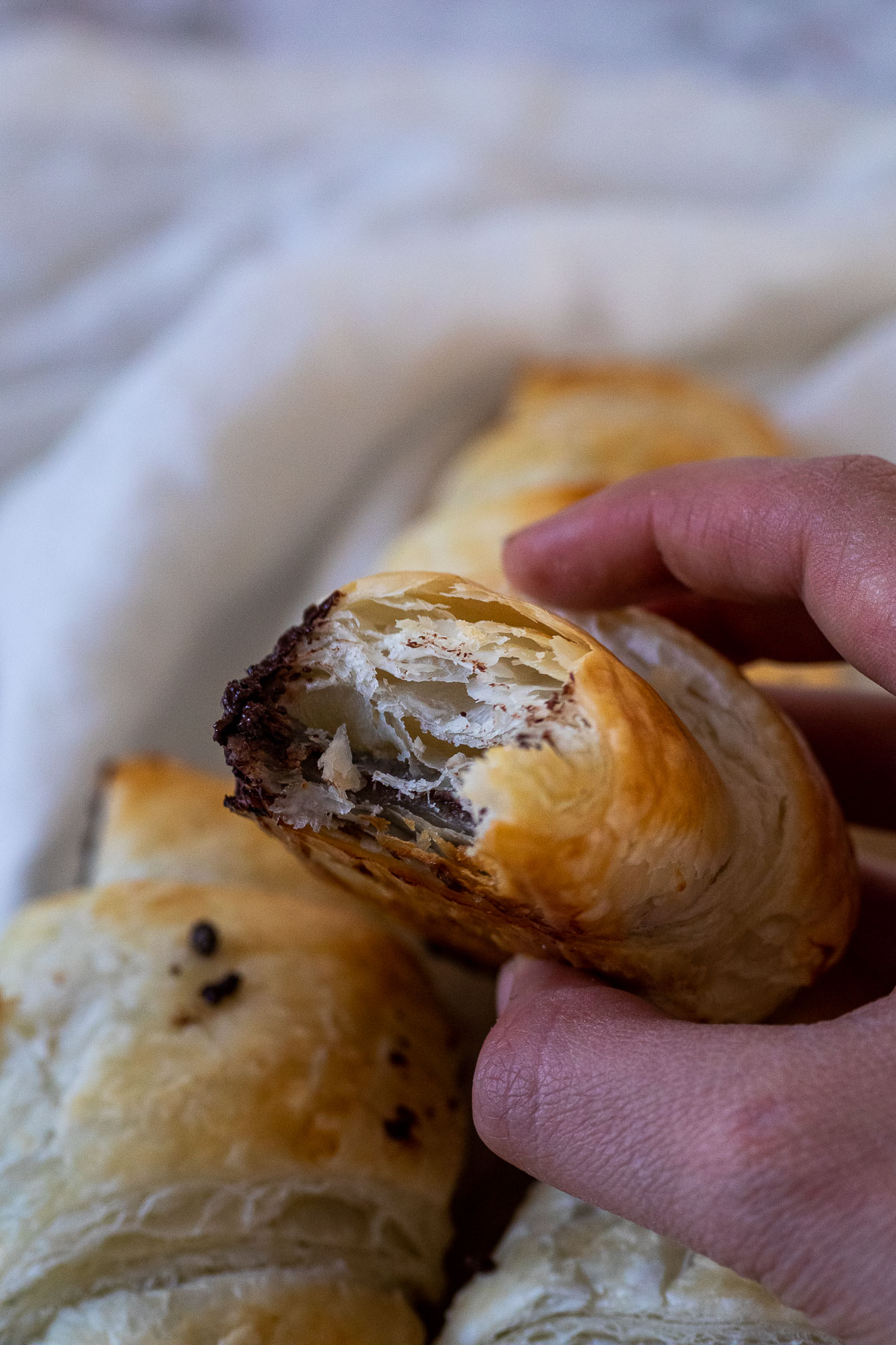 Holding a vegan chocolate croissants with flaky layers