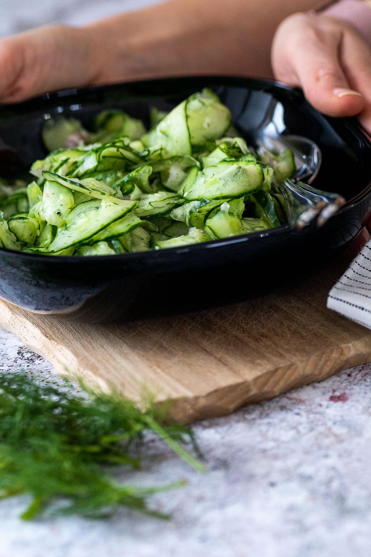 Holding a bowl with cucumber salad with some dill in the front blurred