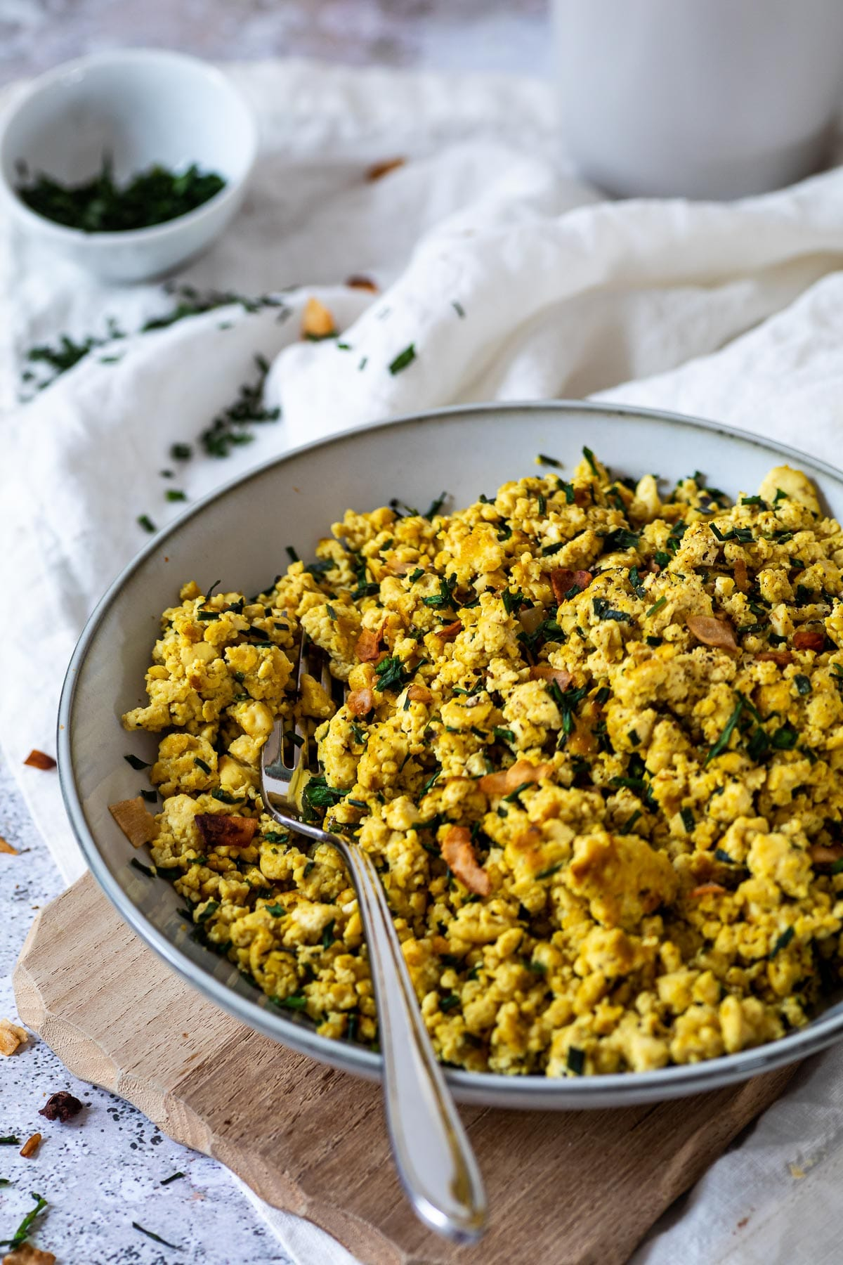 A bowl with scrambled tofu sprinkled with coconut bacon and parsley