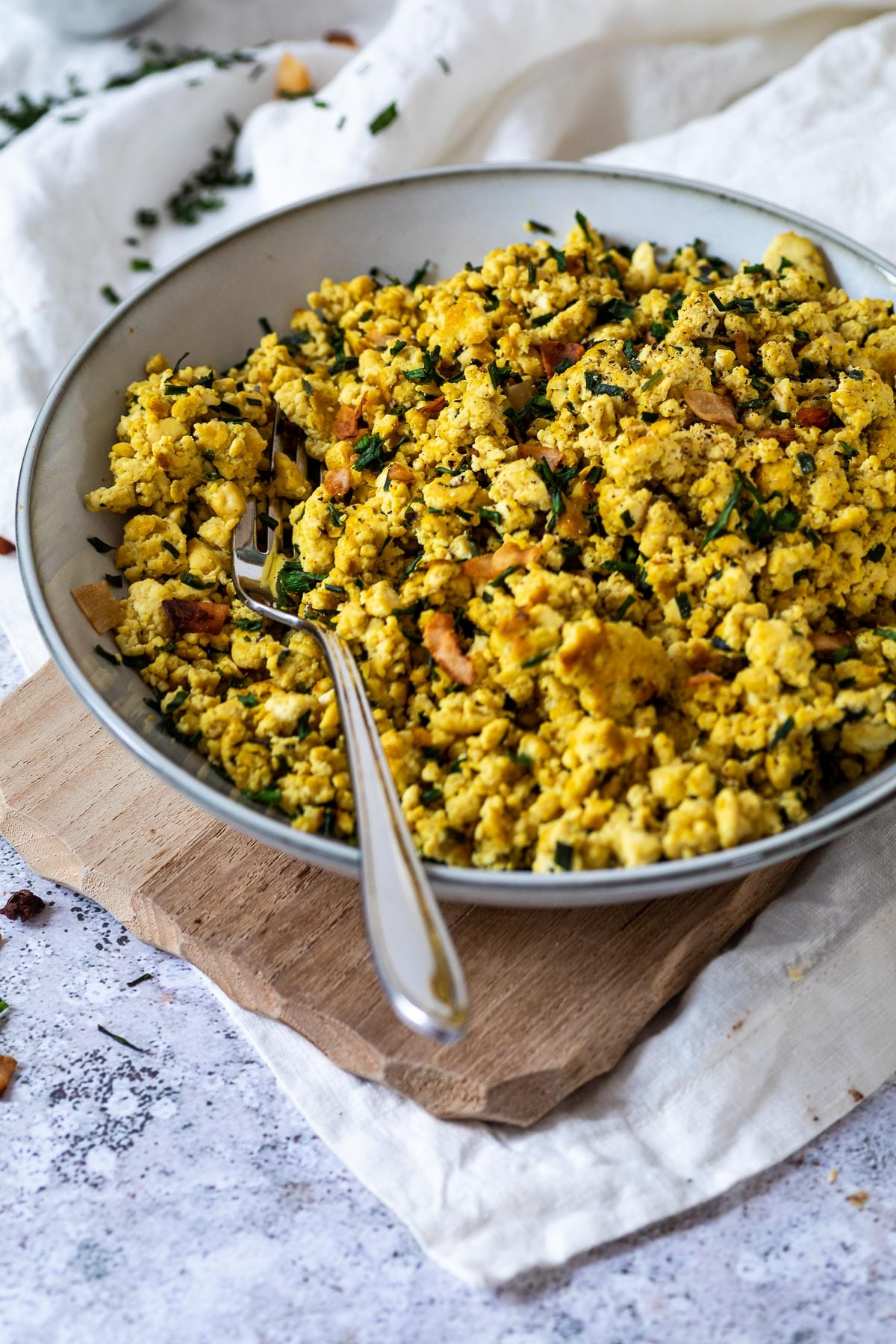 A bowl of vegan scrambled eggs with a fork