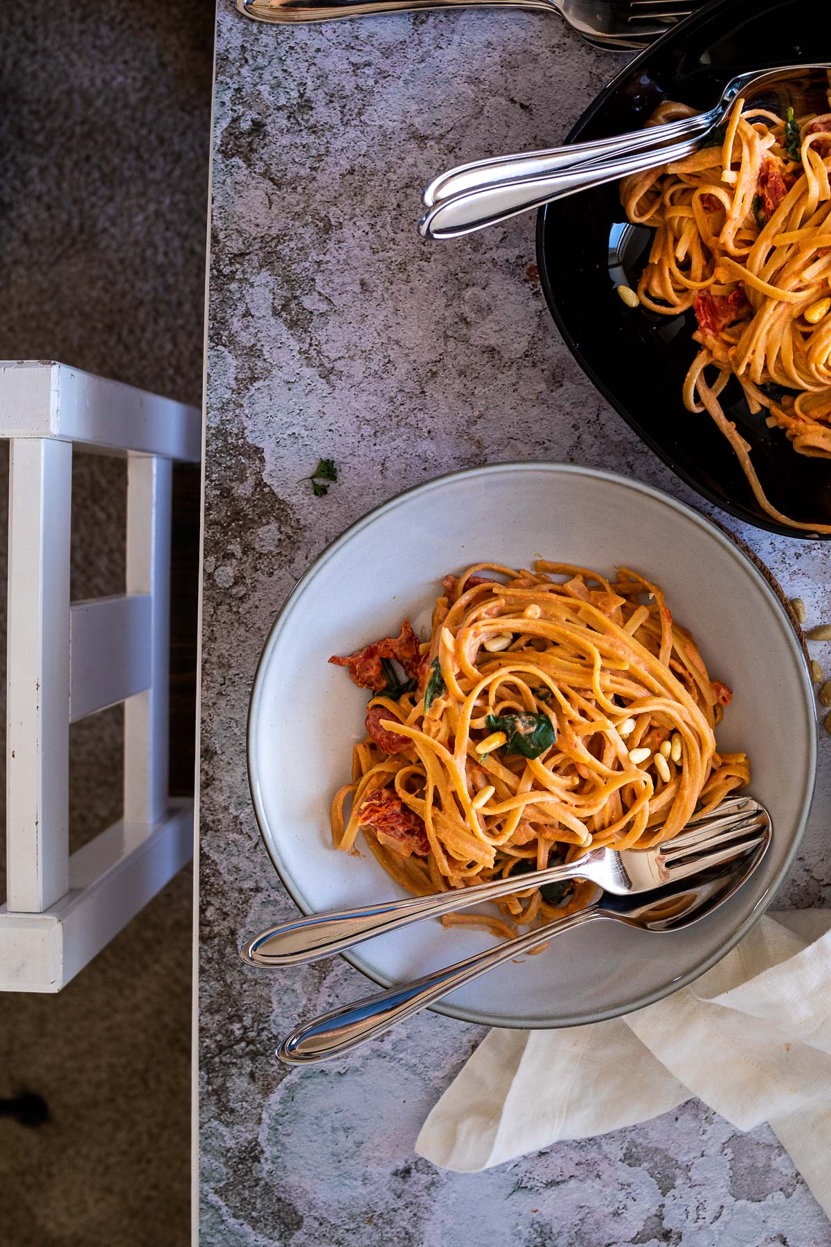 Two tomato alfredo spaghetti bowl with a chair in front