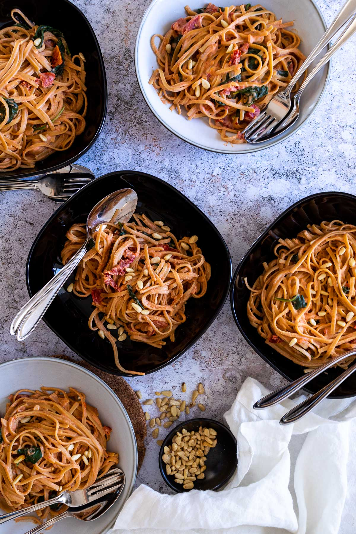 Five bowls with tomato alfredo spaghetti topped with pine nuts